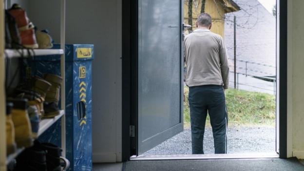 Ein Man steht vor einer Asylunterkunft.