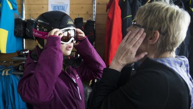 Eine chinesische Touristin probiert mit Hilfe einer Verkäuferin eine Skibrille.