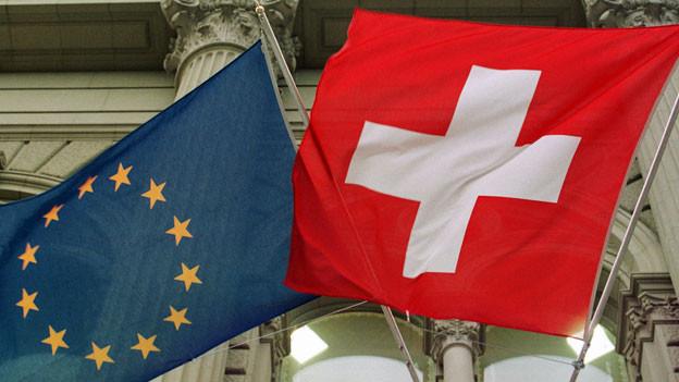 Die Europa- und die Schweizerfahne am Bundeshaus in Bern.