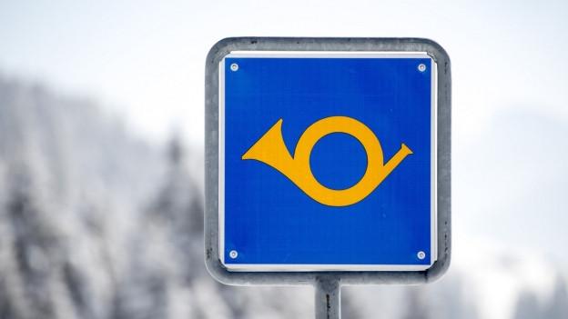 Ein Postautosignalschild vor verschneiter Landschaft.Ein Postautosiganlschild vor verschneiter Landschaft.