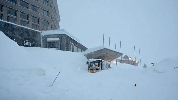Das Bild zeigt das Hotel Säntis und ein Postauto im Schnee.