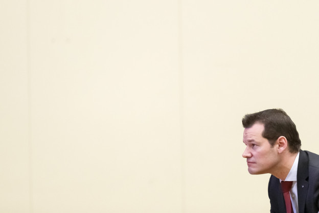 Rechts im Bild ragt ein Mann im Anzug ins Bild.