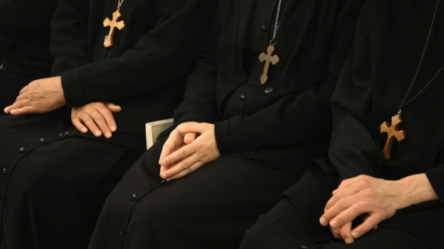 Nonnen sitzen nebeneinander.