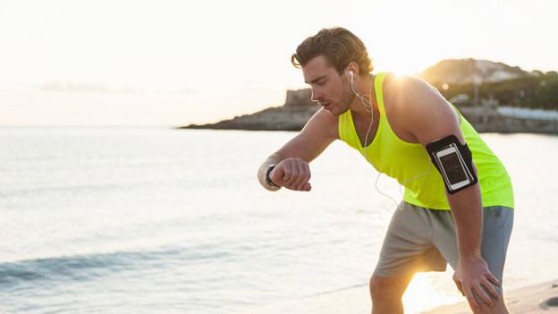 Ein Jogger kontrolliert nach seinem Lauf seinen Puls anhand einer Puls-Messuhr.