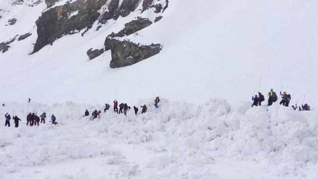 Das Bild zeigt Rettungskräfte bei der Suche nach möglichen Vermissten nach dem Lawinenabgang im Skigebiet von Crans-Montana.