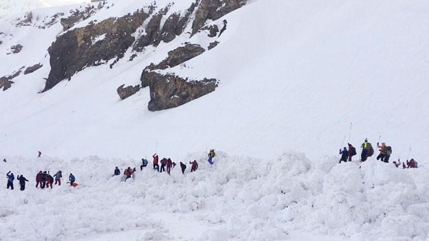 Helfer suchen nach Vermissten unter der Lawine, welche am Dienstag in Crans-Montana im Kanton Wallis niedergegangen ist.