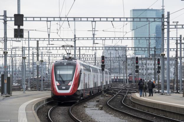 Ein Zug fährt zwischen vielen Kabeln und Masten.