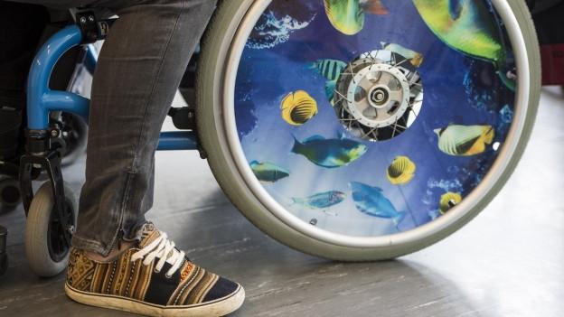 Das Bild zeigt ein Rad eines Rollstuhls und die Beine einer betreuenden Person.