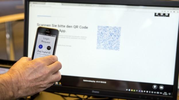 Das Symboldbild zeigt ein Smartphone vor einem Computer.
