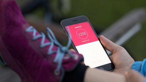 Eine Frau benutzt nach dem Joggen die Helsana+ App. Das Bonusprogramm von Helsana soll Benutzer zum Aktivsein motivieren.