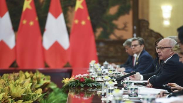 Das Bild zeigt Bundesrat Ueli Maurer mit einer Delegation an einem Tisch, in der Mitte des Bildes sind Flaggen von China und der Schweiz zu sehen.