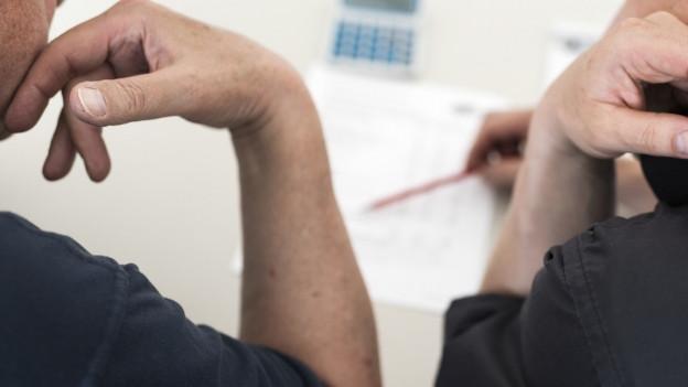 Das Bild zeigt zwei Personen, die gemeinsam etwas auf einem Blatt anschauen.