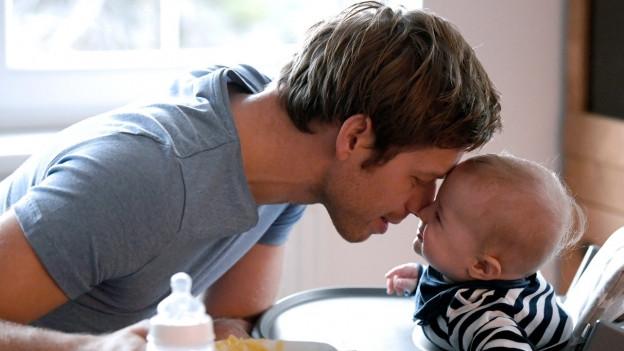 Das Bild zeigt einen Vater mit seinem Baby.