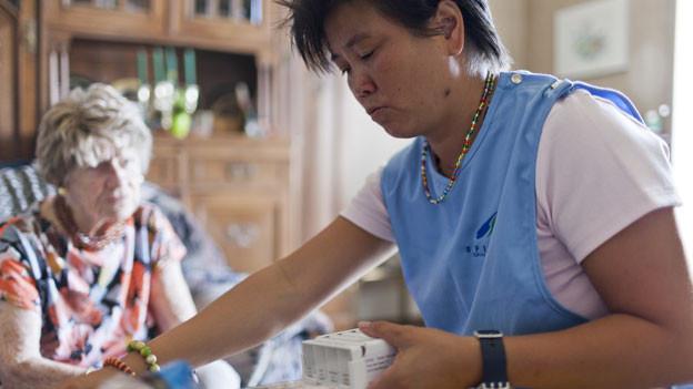 Eine Spitex-Mitarbeiterin pflegt eine ältere Dame zu Hause.