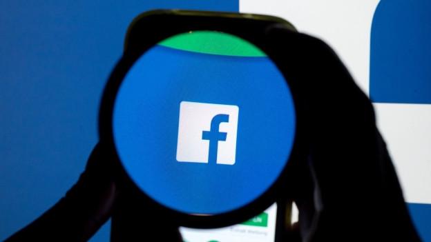 Das Facebook-Logo von einer Lupe hervorgehoben.