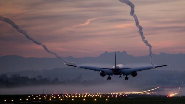 Ein Flugzeug landet bei Morgendämmerung in Zürich.