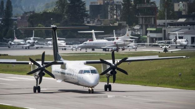 Auf dem Bild ist der Flughafen Lugano-Agno zu sehen und mehrere Flugzeuge.