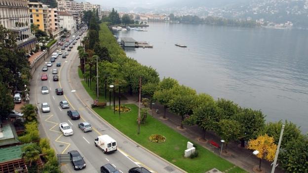 Auf dem Bild ist die Seepromenade in Lugano zu sehen und Autos, die im Stau stehen.
