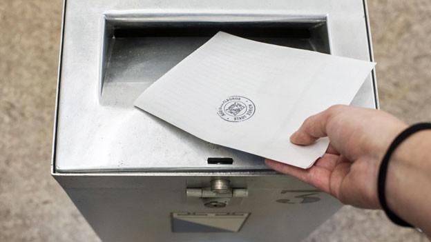 Eine Frau wirft ihre Abstimmungsunterlagen zur Ständerats- und Nationalratswahl in die Urne.
