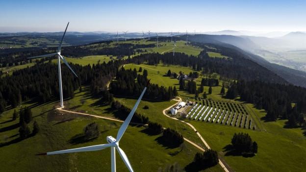 Wind- und Solarenergieanlagen in der Schweizer Landschaft.