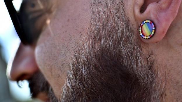 Bei einer Demonstration gegen Homophobie trägt ein Aktivist ein Ohrring in Regenbogenfarben.
