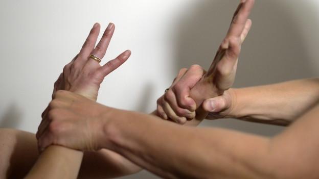 Ein Mann wird handgreiflich seiner Frau gegenüber. Man sieht nur die Hände der Beiden.
