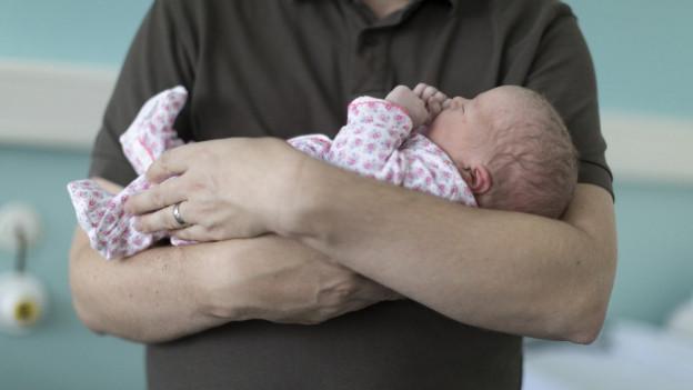 Mann hält ein Baby