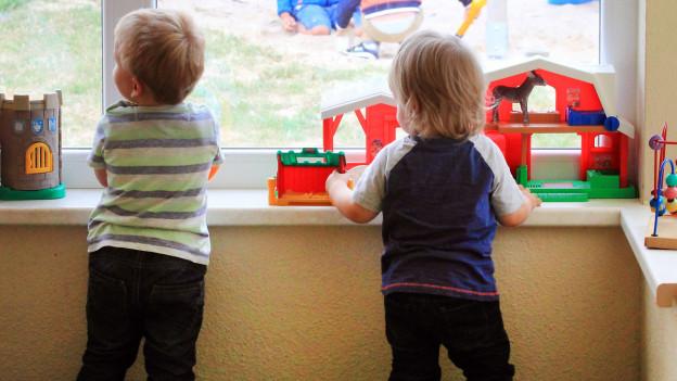 Zwei Kinder schauen in einer Kita aus dem Fenster.