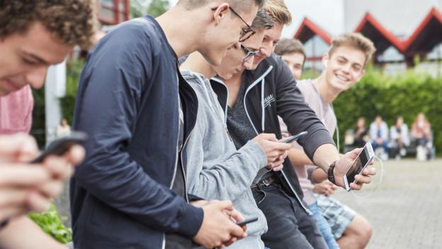 Das Bild zeigt Schülerinnen und Schüler am Handy.