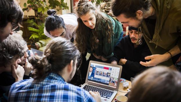 Auf dem Bild sind Vertreter der Klimastreikbewegung in Lausanne zu sehen, die auf den Bildschirm eines Laptops schauen.