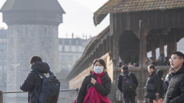 Touristin mit Schutzmaske vor der Luzerner Kapellbrücke