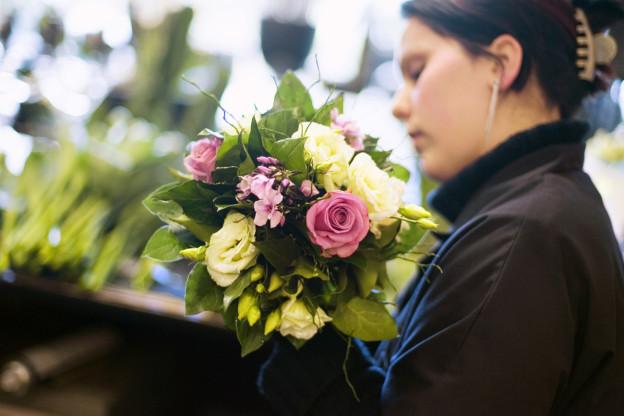 Eine Floristin der Blumenhalle am Pelikanplatz in Zürich bindet einen Strauss.
