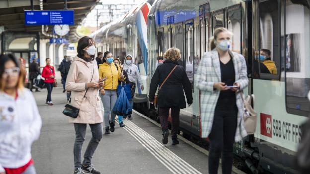 Passagiere auf dem Perron mit Schutzmasken.