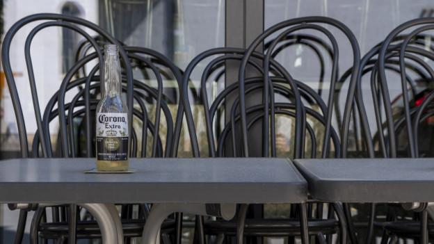 Fast leere Tische und gestapelte Stühle vor einem Restaurant