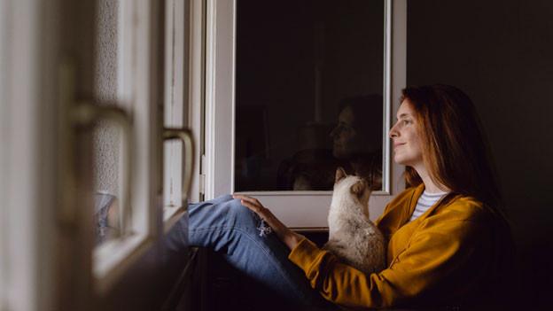 Symbolbild. Junge Frau sitzt mit ihrer Katze vor dem Fenster in ihrer Wohnung.