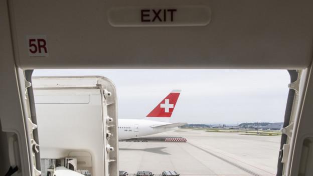 Auf dem Bild ist eine Swiss-Maschine zu sehen - fotografiert aus einer offenen Flugzeugtüre.