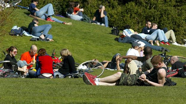 Symbolbild. Menschen tummeln sich in einem Park.