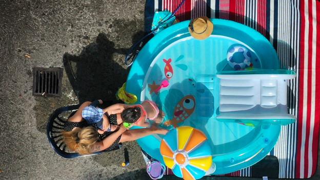 Eine Frau kühlt ihr Kind in einem Pool ab.