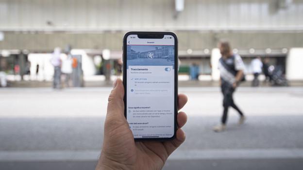 Eine Person hält ihr Smartphone in der Hand, auf der die SwissCovid-App zu sehen ist.
