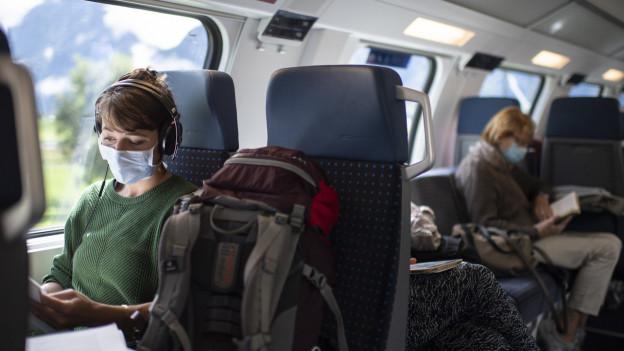 Zu sehen sind Menschen, die in einem Zug sitzen und eine Schutzmaske tragen.