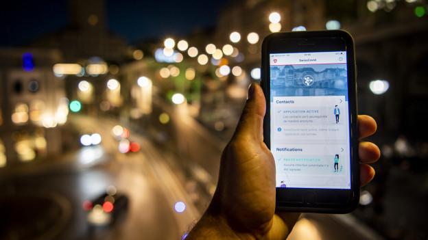 Eine Person hält ein Handy, auf dem die SwissCovid-App zu sehen ist.