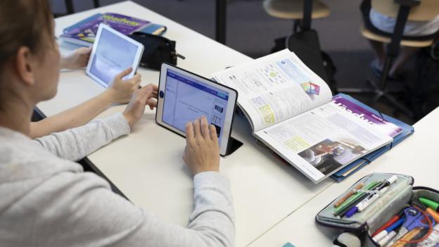 Das Bild zeigt eine Schülerin mit Tablet und Schulheft.