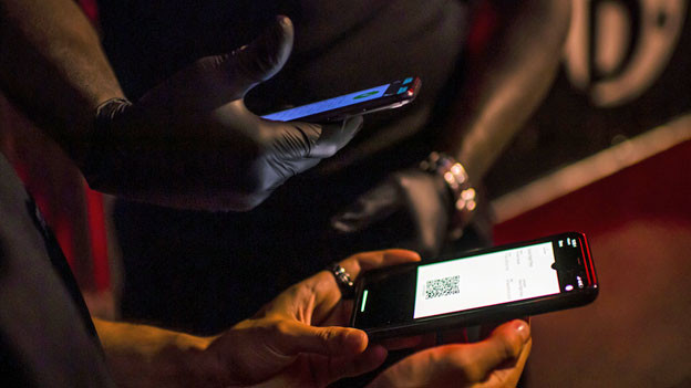 Ein Sicherheitsbeamter scannt den QR-Code der Swiss Pass Night-Anwendung eines Kunden vor einer Diskothek.