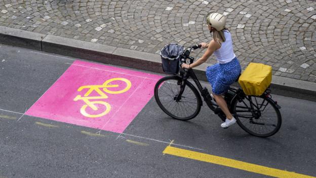 Eine Frau fährt auf einem neu markierten Veloweg.