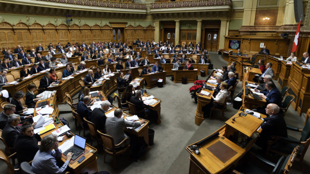 Zu sehen ist der Nationalratssaal, gut gefüllt, mit vielen Politikerinnen und Politikern, während einer Debatte.