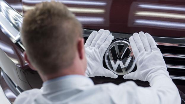 Ein Mitarbeiter kontrolliert im VW-Werk das Logo eines Autos. Der Autokonzern ist in den USA wegen angeblicher Schadstoff-Manipulationen unter Druck.