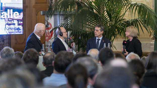 Aussenminister Ignazio Cassis, APK-Präsidentin Elisabeth Schneider-Schneiter und Historiker Georg Kreis werden von SRF-Bundeshausredaktor Philipp Burkhardt befragt.