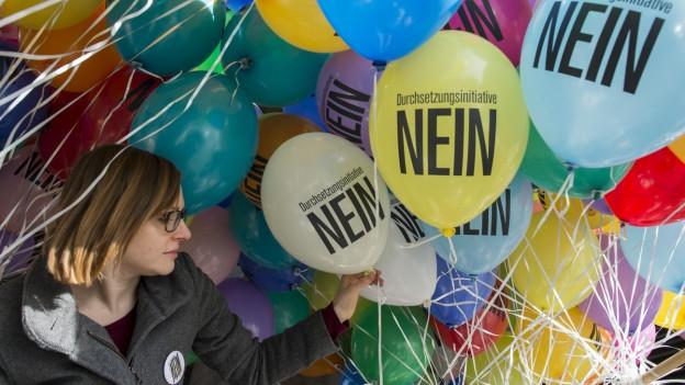 Eine Frau bläst Ballone auf gegen die Durchsetzungsinitiative.