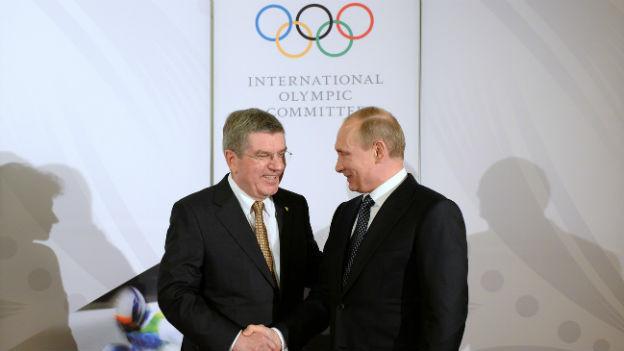IOC-Präsident Thomas Bach und Vladimir Putin schütteln die Hände, dahinter eine weisse Wand mit den Olympischen Ringen.