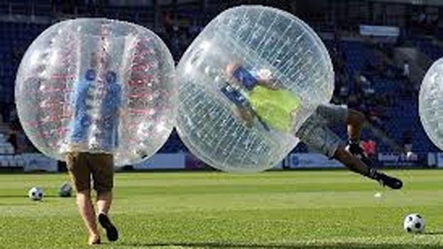Zwei Fussballer spielen Bubble Soccer.